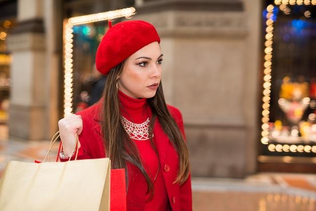 Lächelnde junge frau in einer stadt vor weihnachten einkaufen Premium Fotos