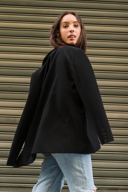 Lächelnde junge frau mit der schwarzen jacke, die vor eisenfensterladen steht Kostenlose Fotos