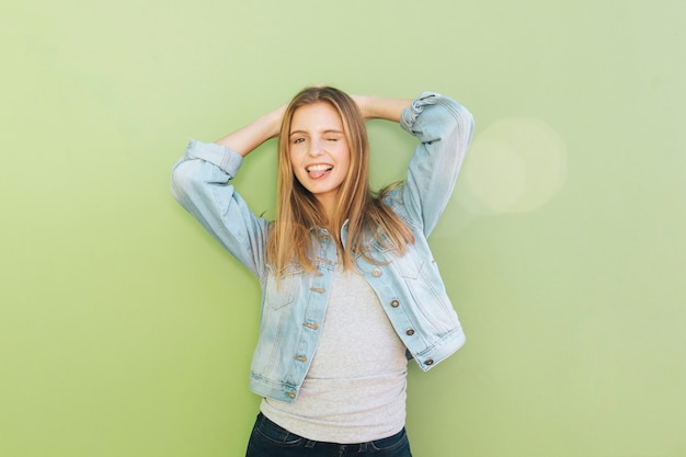 Lächelnde junge frau mit ihren händen hinter dem kopf, der gegen grünen hintergrund blinzelt Kostenlose Fotos