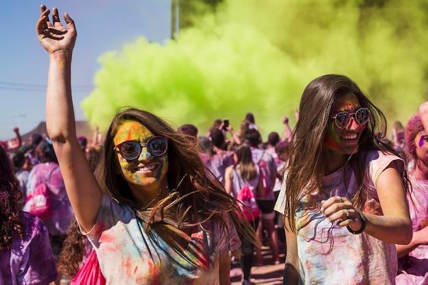 Lächelnde junge frauen, die in das holi festival tanzen Kostenlose Fotos