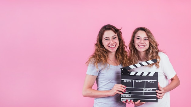 Lächelnde junge frauen, die scharnierventilbrett in den händen gegen rosa hintergrund halten Kostenlose Fotos