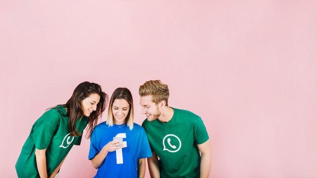 Lächelnde junge freunde, die smartphone gegen rosa hintergrund betrachten Kostenlose Fotos