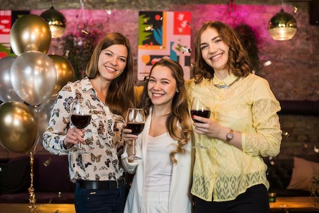 Lächelnde junge freundinnen in der bar getränke genießend Kostenlose Fotos