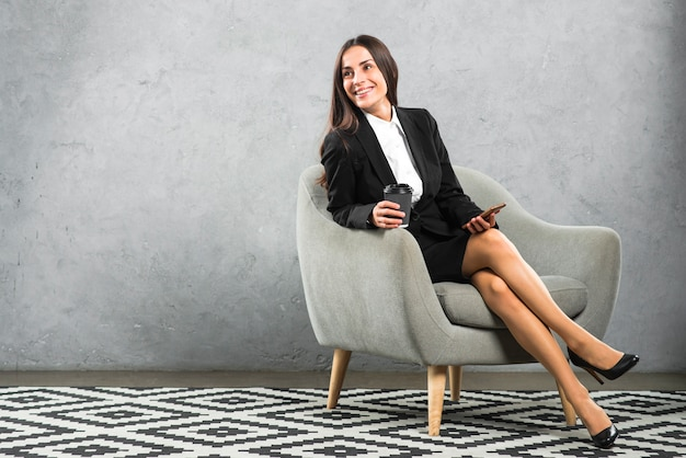 Lächelnde junge geschäftsfrau, die auf dem lehnsessel hält wegwerfkaffeetasse und mobiltelefon sitzt Kostenlose Fotos