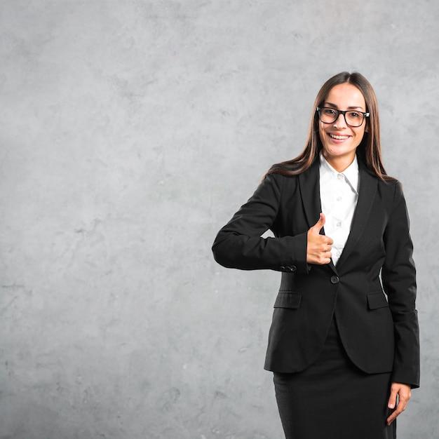 Lächelnde junge geschäftsfrau, die daumen herauf zeichen gegen konkreten hintergrund zeigt Kostenlose Fotos