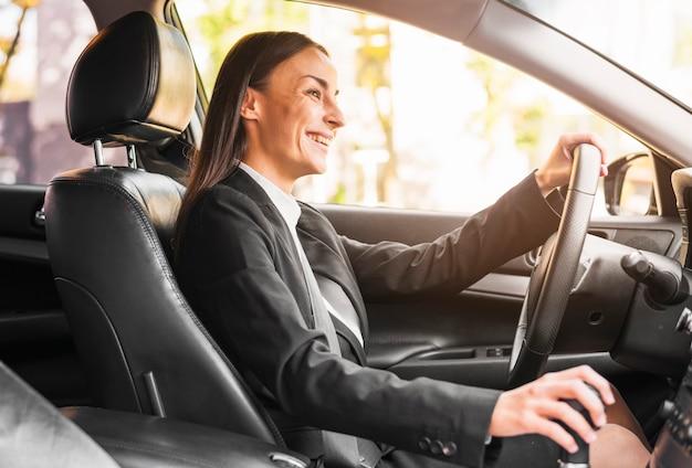 Lächelnde junge geschäftsfrau, die ein auto antreibt Kostenlose Fotos