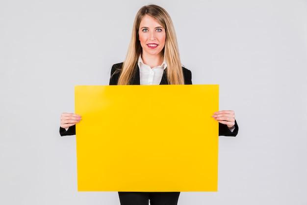 Lächelnde junge geschäftsfrau, die gelbes leeres plakat gegen grauen hintergrund hält Kostenlose Fotos