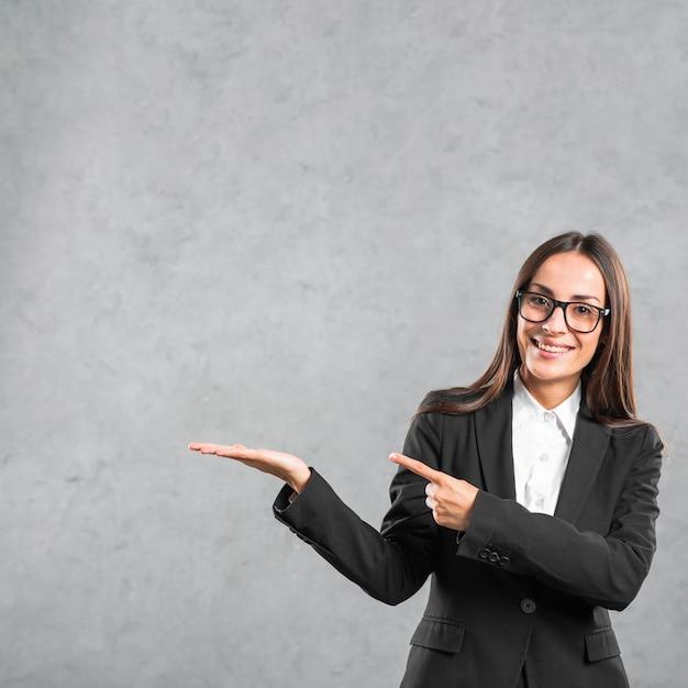 Lächelnde junge geschäftsfrau, die ihren finger in richtung zum darstellen des produktes zeigt Kostenlose Fotos