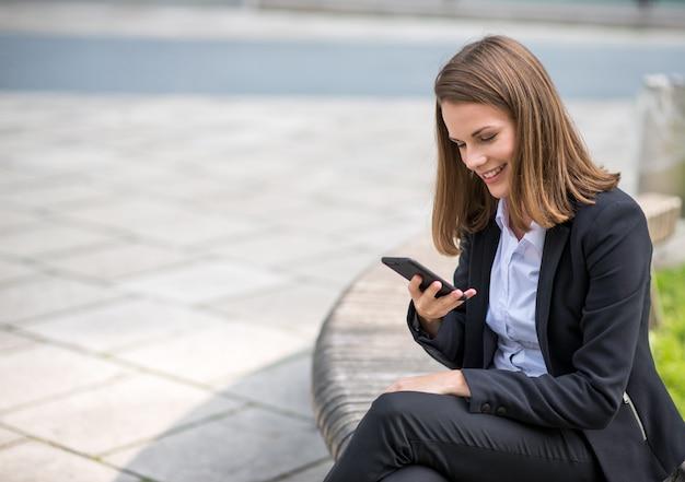 Lächelnde junge geschäftsfrau, die ihren mobilhandy verwendet Premium Fotos