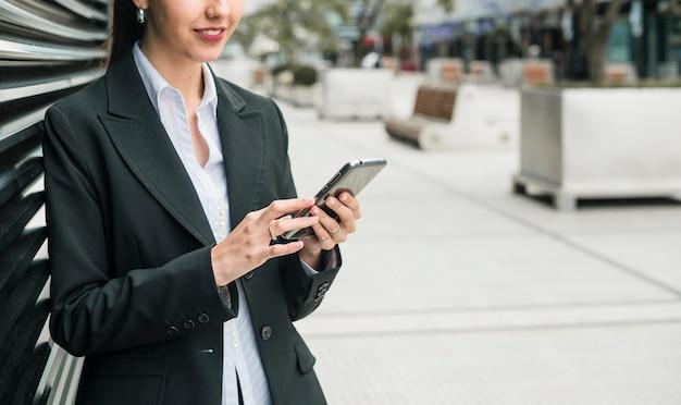 Lächelnde junge geschäftsfrau, die intelligentes telefon verwendet Kostenlose Fotos