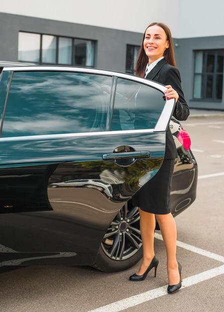 Lächelnde junge geschäftsfrau, die mit ihrem schwarzen auto steht Kostenlose Fotos