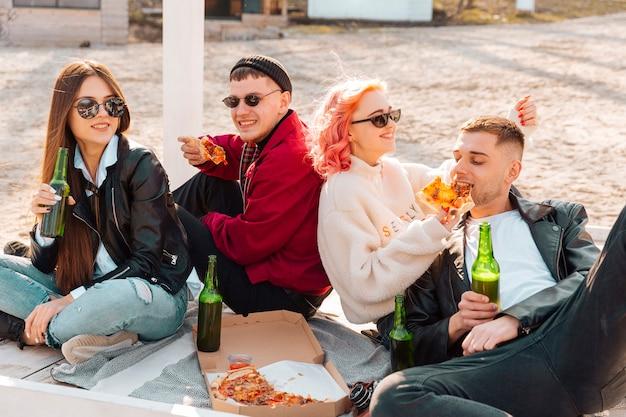 Lächelnde junge hippies, die auf dem boden mit bier und pizza sitzen Kostenlose Fotos