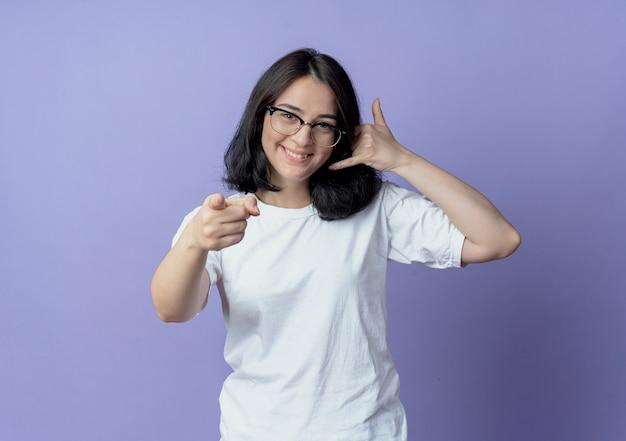 Lächelnde junge hübsche frau, die eine brille trägt, die anrufgeste tut und nach vorne zeigt Kostenlose Fotos
