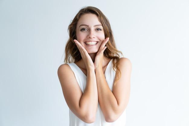 Lächelnde junge hübsche frau, die kamera und rührendes gesicht betrachtet Kostenlose Fotos