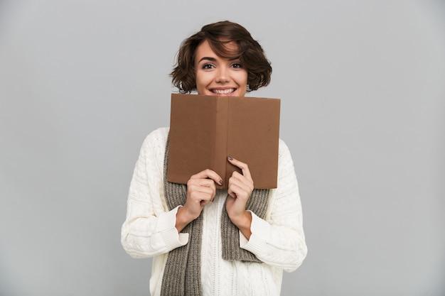 Lächelnde junge hübsche frau, die schal liest buch trägt. Kostenlose Fotos