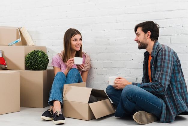 Lächelnde junge paare, die auf boden mit den beweglichen pappschachteln den kaffee trinken sitzen Kostenlose Fotos