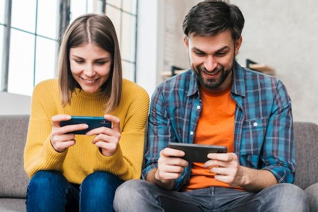 Lächelnde junge paare, die auf dem sofa spielt das videospiel am handy sitzen Kostenlose Fotos