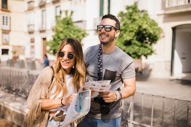 Lächelnde junge paare, die auf der straße hält karte stehen Kostenlose Fotos
