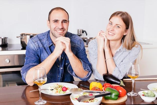 Lächelnde junge paare, die das frühstück zusammen schauen zur kamera haben Kostenlose Fotos