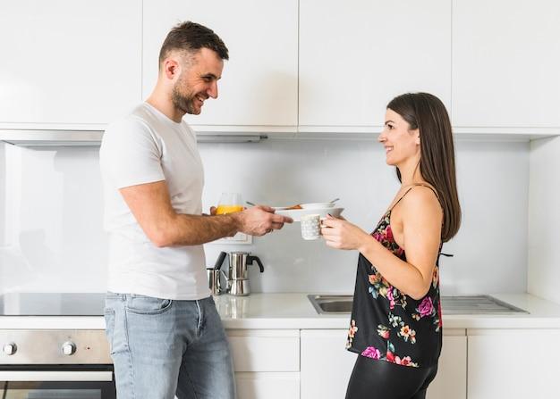 Lächelnde junge paare, die in der küche frühstücken Kostenlose Fotos