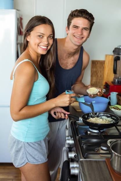 Lächelnde junge paare, die lebensmittel in der küche kochen Premium Fotos