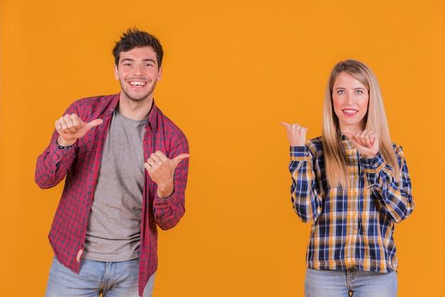 Lächelnde junge paare, die miteinander daumengeste gegen einen orange hintergrund machen Kostenlose Fotos