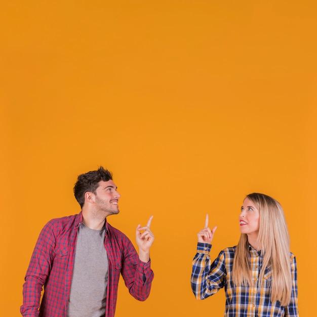 Lächelnde junge paare, die oben schauen und aufwärts ihren finger gegen einen orange hintergrund zeigen Kostenlose Fotos