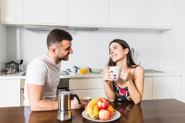 Lächelnde junge paare, die zusammen in der küche genießt den kaffee sitzen Kostenlose Fotos