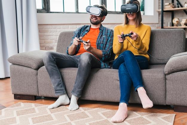 Lächelnde junge paare, welche die gläser der virtuellen realität spielen das videospiel tragen Kostenlose Fotos
