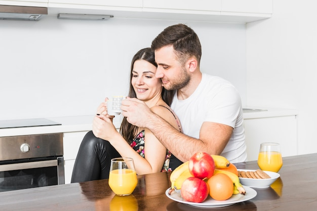 Lächelnde junge paare, welche die kaffeetasse beim frühstücken klirren Kostenlose Fotos