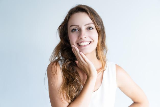 Lächelnde junge reizende frau, die kamera und rührendes gesicht betrachtet Kostenlose Fotos