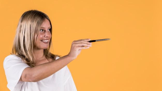 Lächelnde junge sperrungsfrau, die das darstellen des gestikulierens mit behälter über hellem hintergrund zeigt Kostenlose Fotos