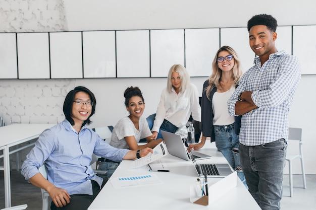 Lächelnde junge webentwickler, die mit laptops am tisch posieren. innenporträt des asiatischen studenten mit den schwarzen haaren, die zeit mit freunden in der universität verbringen. Kostenlose Fotos