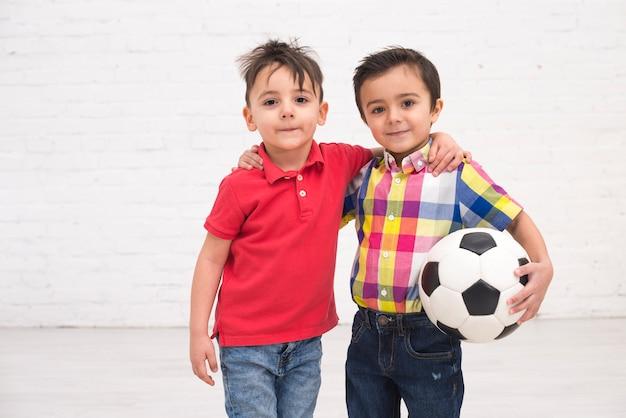 Lächelnde jungen mit einem fußballball Kostenlose Fotos