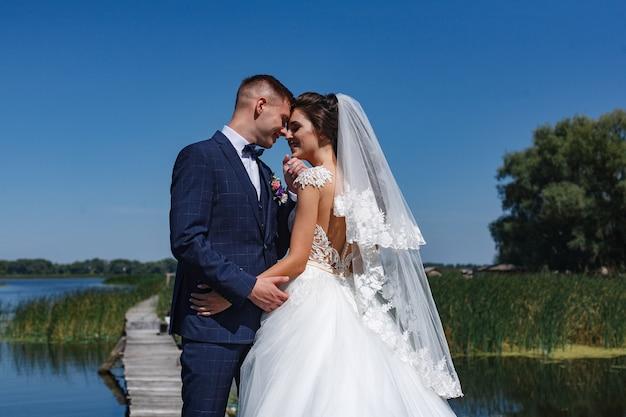 Lächelnde jungvermählten schauen sich sanft an und umarmen sich. porträt ein hochzeitspaar, das auf holzbrücke nahe fluss geht. Premium Fotos