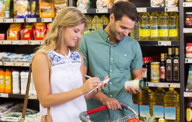Lächelnde kaufende lebensmittelprodukte der hellen paare und schreiben auf notizbuch Premium Fotos
