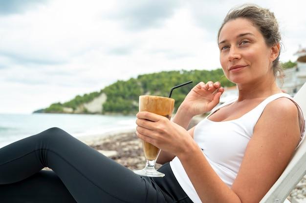 Lächelnde kaukasische frau, die kaffeegetränk an einem strand mit schaum und trinkhalm mit hügeln hält Kostenlose Fotos