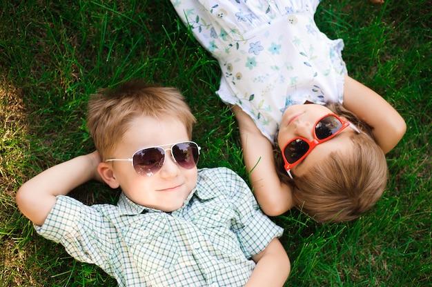 Lächelnde kinder im garten mit sonnenbrille Premium Fotos