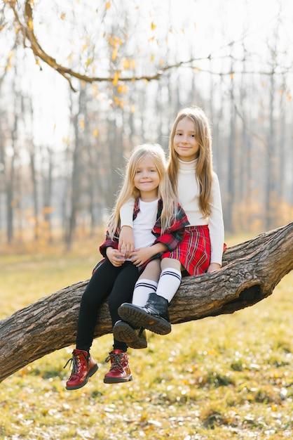 Lächelnde kinder sitzen auf einem baum im herbstpark Premium Fotos