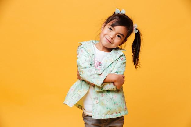 Lächelnde kindstellung des kleinen mädchens lokalisiert Kostenlose Fotos