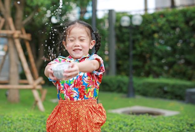 Lächelnde kleine asiatische thailändische kinder im thailändischen zeitraumkleid, das wasser im songkran festival spritzt Premium Fotos
