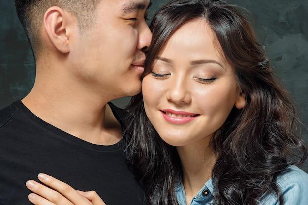 Lächelnde koreanische paare auf grau Kostenlose Fotos