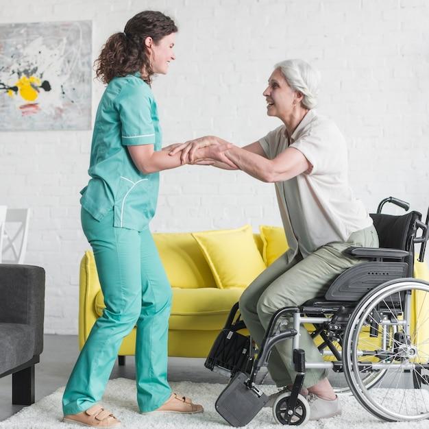 Lächelnde krankenschwester, die älterem weiblichem patienten hilft, vom rollstuhl herauszukommen Kostenlose Fotos