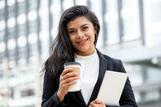 Lächelnde latinogeschäftsfrau, die kaffeetasse und tablet-computer hält Premium Fotos