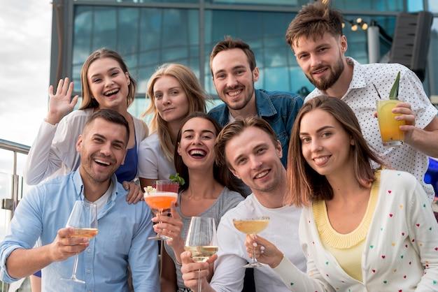 Lächelnde leute, die an einer party aufwerfen Kostenlose Fotos