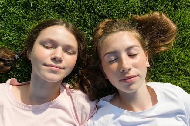 Lächelnde mädchen mit den geschlossenen augen, die auf grünem gras liegen. Premium Fotos