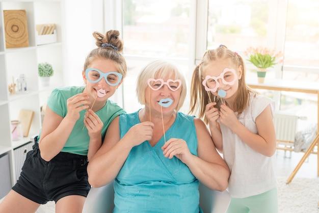 Lächelnde mädchen und ältere frau mit papiergläsern und