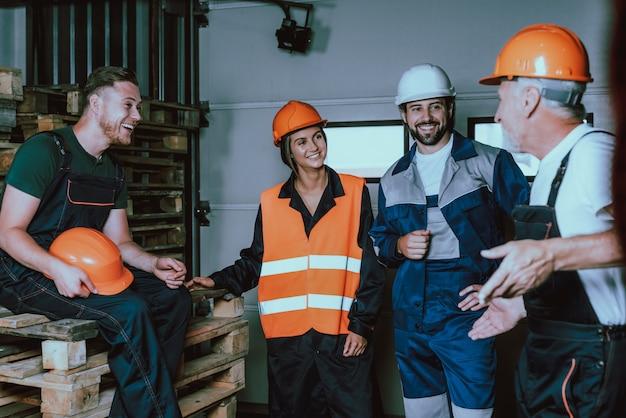 Lächelnde menschen in uniform und schutzhelmen in der pause Premium Fotos