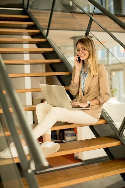 Lächelnde moderne geschäftsfrau, die auf der treppe im büro sitzt, am notizbuch arbeitet und auf handy spricht Premium Fotos