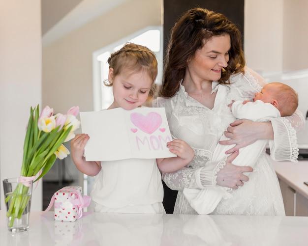 Lächelnde mutter, die ihr baby während tochter hält grußkarte trägt Kostenlose Fotos